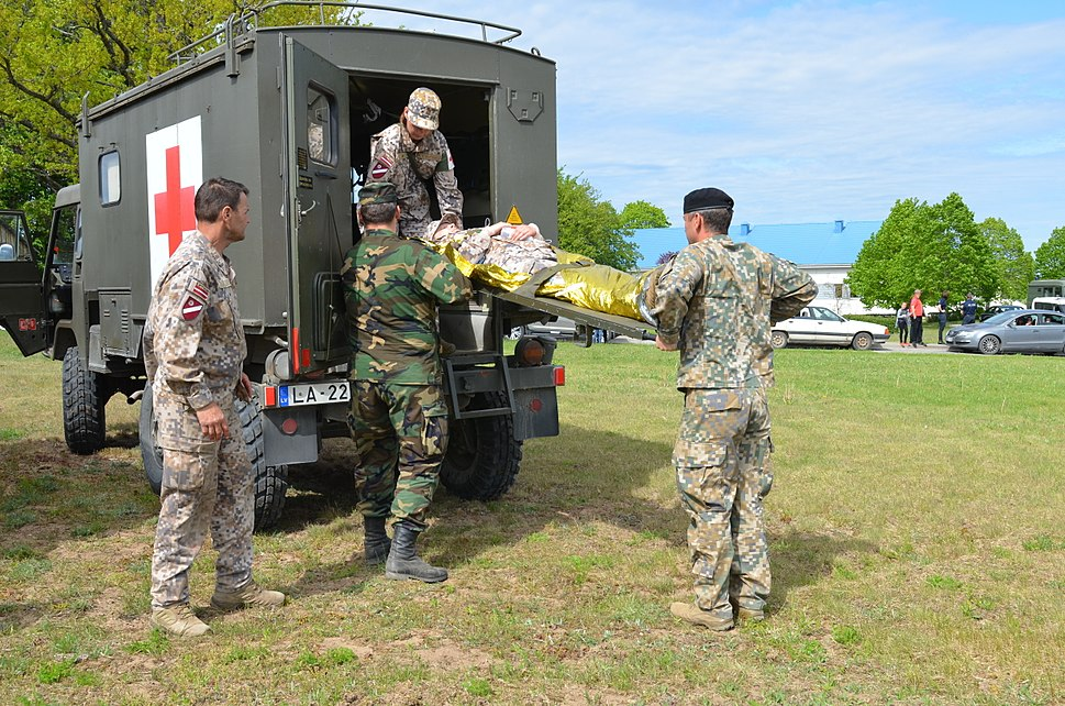 Members of the Latvian Zemessardze or National Guard 45th Logistics Battalion, remove a volunteer patient from a military ambulance in a field