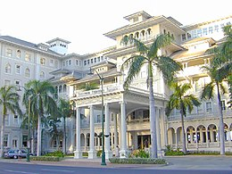 Starwood Sheraton Moana Surfrider Hotel, with a front side made of white stone decorated with arches and round pillars, with palm trees in front of the building.