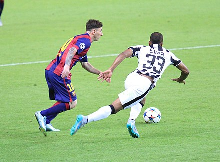 "Messi dribbling past Juventus defender Patrice Evra during the UEFA Champions League Final in June 2015. Prior to the match, Juventus captain Gianluigi Buffon stated, ""Messi is an alien that dedicates himself to playing with humans"". Moment of the Champions League final FC Barcelona - Juventus 2015.jpg"
