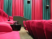 Interior of a Hoyts movie theater in Australia, with stadium seating, acoustic wall hangings, wall-mounted speakers, and cup holders.