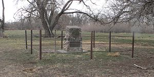 Stone monument about 3 feet high, on flat ground near wooded creek