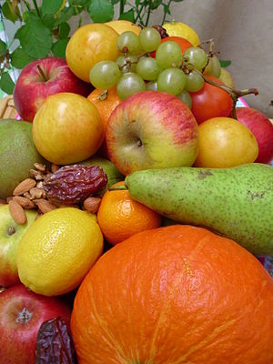 Fruitarianism - Close-up of a fruit bowl with apples, grapes, prunes, nuts, dates, tomatoes, lemons, mandarins, pears, and a pumpkin