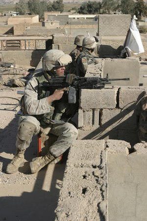 Operation Steel Curtain - A U.S. Marine and Iraqi Army soldiers watch over the surrounding streets from a rooftop in Karabilah, Iraq, during Operation Steel Curtain on 11 November 2005.