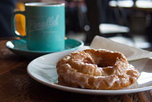 An old-fashioned doughnut with a sugar glaze, accompanied with coffee