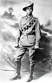 An Aboriginal soldier wearing a slouch hat, leather chest pouches and riding boots, holding a cane