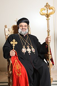 Publicity shot of His Holiness Patriarch Moran Mor Ignatius Aphrem II standing and in color.