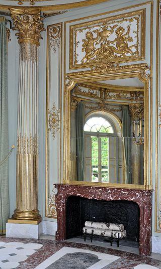 Cloison vers le réchauffoir portant un miroir et une cheminée.