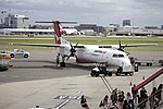 QantasLink (VH-QOC) Bombardier Dash 8 Q400 at the domestic terminal, with Qantas (VH-OQL) Airbus A380-842 at the international terminal in the backgound, at Sydney Airport.jpg