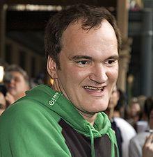 Photo de Quentin Tarantino s'arrêtant à la poitrine. Il sourit et porte une veste de jogging.