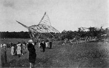 A photograph showing the wreckage of R101 in the background with a number of onlookers to the left of the image
