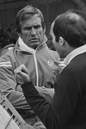 Photograph of Carlos Reutemann in the background in conversation with Frank Williams, visible in the foreground with his head turned away from the camera.
