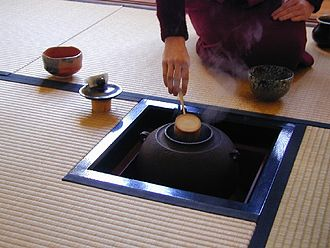 Japanese tea ceremony - The ro season; a host rests a bamboo ladle on an iron pot that rests inside the ro)