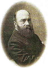 Middle-aged man with a bald head and a bushy dark beard