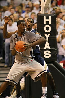 """A African-American teenage basketball player wearing a gray uniform looks over his shoulder at another playing in a blue uniform. Behind them are fans and a basketball hoop with the word """"HOYAS"""" on it."""