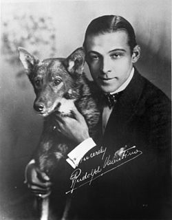A black and white photograph of Rudolph Valentino with his dog; Valentino wears a dark suit and bow tie and is shown from the waist up, looking at the camera. The photograph has his autograph in white.