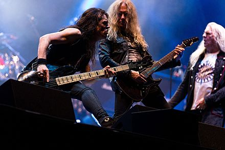 "Bassist Tim ""Nibbs"" Carter and guitarist Doug Scarratt at the Rockharz 2016 (Biff Byford in the background) Saxon Rockharz 2016 24.jpg"