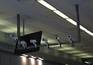 Mass surveillance in the United Kingdom - A bank of seven closed-circuit television cameras monitoring people exiting Birmigham New Street, a major British railway station.