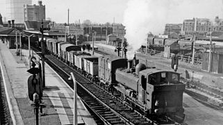 A pannier tank locomotive, travelling in reverse, is pulling a train of open and closed goods wagons through a station.