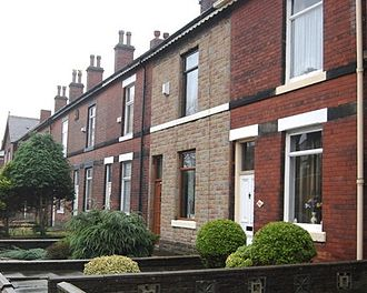 Stone cladding - A row of Victorian, brick-built terraced houses in Bury, Greater Manchester, England (2008). One of the houses has been stone-clad
