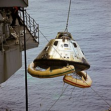 A spacecraft is lifted in the air onto a ship