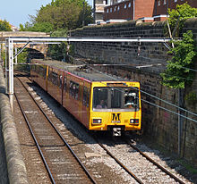 Yellow passenger train next to a stone wall