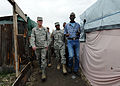 U.S. Air Force Gen. Douglas Fraser, commander of U.S. Southern Command, is greeted by a camp leader and taken for a walk through Ancien Aeroport Militaire in Port-au-Prince, Haiti, March 6, 2010 100306-N-HX866-013.jpg