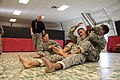 U.S. Navy Intelligence Specialist 1st Class Daniel Baudin, right, applies a submission move on Hospitalman Brian Mays as U.S. Army Sgt. 1st Class Roger Lumen, standing, a modern Army combatives instructor with 120828-N-IE116-062.jpg