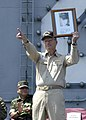 US Navy 050203-N-0499M-100 Commander Carrier Strike Group Nine (CSG-9), Rear Adm. Doug Crowder points to sailors gathered on the flight deck while holding a framed photo of an Indonesian women holding a sign.jpg