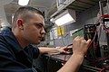 US Navy 070713-N-1730J-087 Aviation Electronics Technician Airman Apprentice Kevin Spires troubleshoots a circuit board with a digital multimeter in the calibration lab aboard nuclear-powered aircraft carrier USS Nimitz (CVN 68.jpg