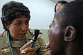 US Navy 071003-N-4238B-032 Cmdr. Sandra Hearn, a pediatric nurse attached to Military Sealift Command hospital ship USNS Comfort (T-AH 20), inspects a patient's throat at the Youth Dental Foundation.jpg