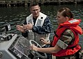 US Navy 100503-N-5019M-003 Boatswain's Mate 1st Class William Geurin instructs Master-At-Arms Seaman Katelyn Tedeschi on how to maneuver a rigid-hull inflatable boat.jpg
