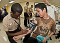 US Navy 101215-N-3620L-021 A Sailor shows Southern High School students how to take a blood pressure reading during Military Day at the school.jpg
