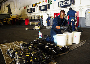 US Navy 111227-N-SK590-106 A Sailor cleans the self-contained breathing apparatus masks.jpg