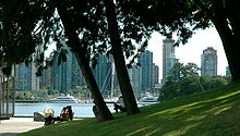 A green grassy hill dotted with trees slopes down to a paved area with benches. Beyond lies water, docks, and a yacht, and skyscrapers.