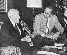 A black-and-white photograph of two men sitting by a low table talking to each other. The man on the left is much older, has white hair, and is wearing a dark suit with a white shirt and a dark tie. He sitting on a plaid couch and gesturing with his right hand as he speaks. The man on the left is younger, has dark hair, and is wearing a light jacket, dark pants, a white shirt and a patterned tie. He is sitting on a chair with his arms resting on his legs as he leans forward to listen to the other man.