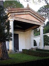 Photographie de la reconstitution, dans un parc boisé, d'un petit temple étrusque avec un fronton porté par deux colonnes et une architrave avec des bas-reliefs.