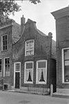 foto van Pand met verminkte pilastergevel onder een kap gebracht met nr. 21