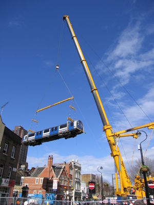 A Waterloo & City Line train being lifted off the line by crane.