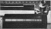 Cylinder on Dictaphone dictation machine. The recording head moved R-L.  The black lines are shiny gaps between tracks.  Wax cylinders could record 1200-1500 words.  They could be reused 100-120 times by putting them in a machine that erased them by 'shaving' off the surface.