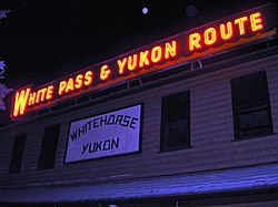 "A red electric sign is seen at night, displaying words ""White Pass & Yukon Route"" above a white, wooden sign emblazoned with ""Whitehorse Yukon""."