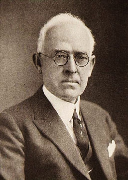 A black-and-white photo of a middle-aged Anglo man with white receding hair, round-rimmed glasses and a somewhat serious expression, wearing a dark tie and sport coat.