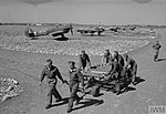 Yugoslav groundcrew wheel a trolley of 3-inch rocket projectiles past re-armed Hawker Hurricane Mark IVs of No. 351 (Yugoslav) Squadron RAF in their dispersals at Prkos, Yugoslavia.jpg
