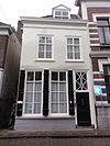 foto van Huis met gepleisterde lijstgevel met dakkapel, schuiframen bovenlicht met elkaar kruisende segmenten
