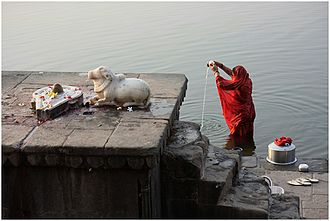 Shaivism - Shaiva icons and a Hindu woman praying in River Narmada, Maheshwar, Madhya Pradesh.