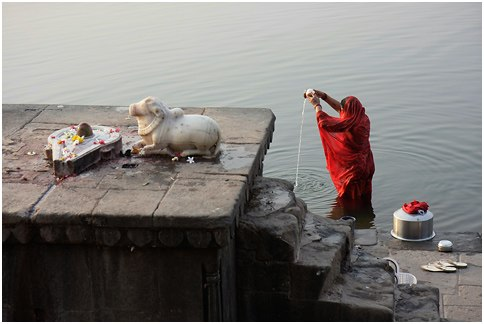 (1) An Indian woman offering puja to the morning sun