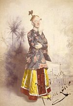 Colourised photograph a man standing in a yellow skirt and patterned silk top, with his hair worn in a comical topknot and chin resting on one finger, looking sideways towards the viewer