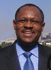 An African-American male with a mustache and glasses wearing a black suit, a blue shirt with white stripes, and a blue tie with silver lines smiles in front of a city skyline.