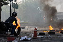 A person pushing burning tyres onto a street