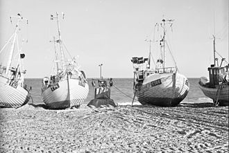 Fishing industry in Denmark - Fishing boats drawn up on the beach at Lild Strand, North Western Jutland, Denmark.