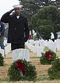 A Sailor salutes after laying a wreath on a grave during the National Wreaths Across America Day. (30902773124).jpg